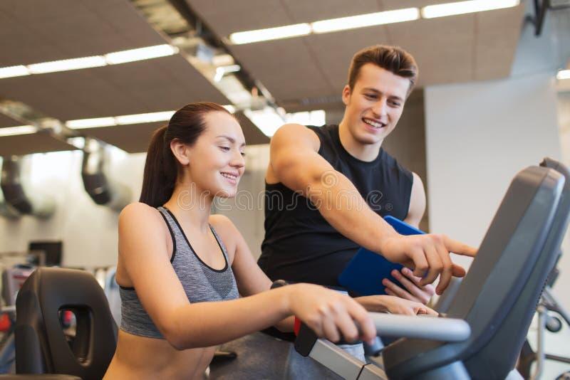 Femme heureuse avec l'entraîneur sur le vélo d'exercice dans le gymnase photographie stock