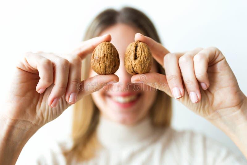 Femme heureuse avec la belle bouche saine tenant l'avant de noix des yeux sur le fond blanc image stock