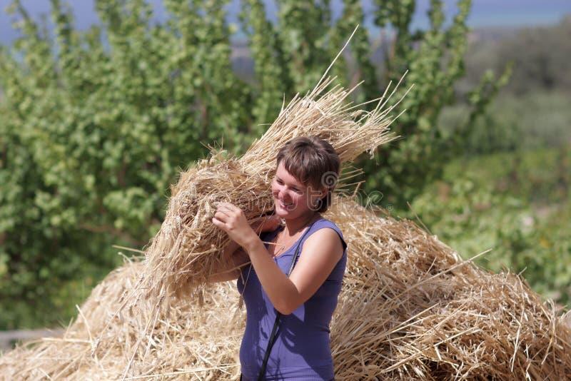 Femme heureuse avec la bracée de blé photographie stock libre de droits