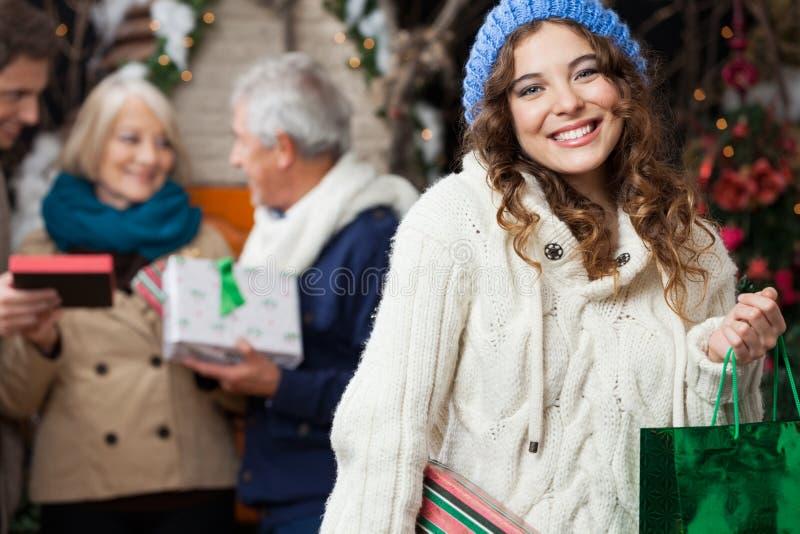 Femme heureuse avec la famille dans le magasin de Noël photo libre de droits