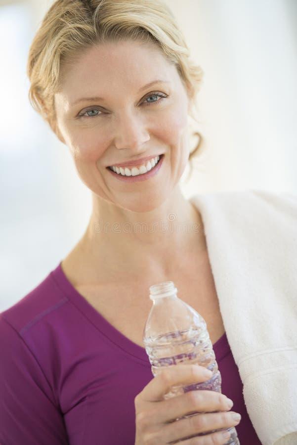 Femme heureuse avec la serviette et la bouteille de l'eau dans le gymnase photo libre de droits