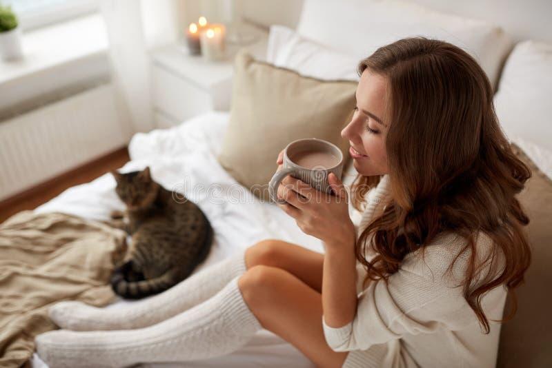 Femme heureuse avec la tasse de café dans le lit à la maison photo libre de droits