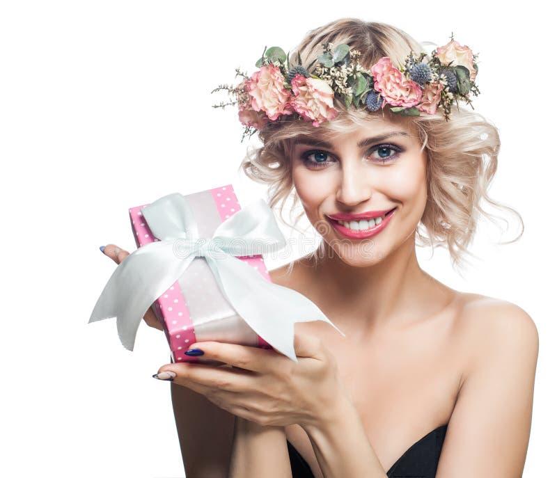 Femme heureuse avec le boîte-cadeau et les fleurs d'isolement sur le blanc photos stock