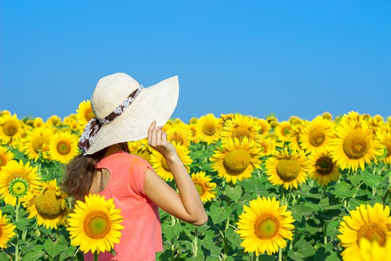 Femme heureuse avec le chapeau de paille dans le domaine de tournesol images stock