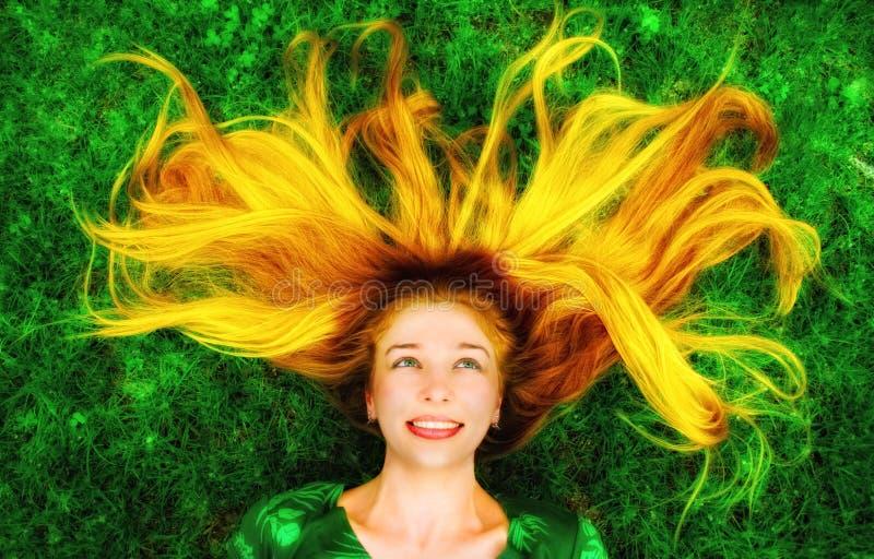 Femme heureuse avec le long cheveu vers le bas sur l'herbe photos libres de droits