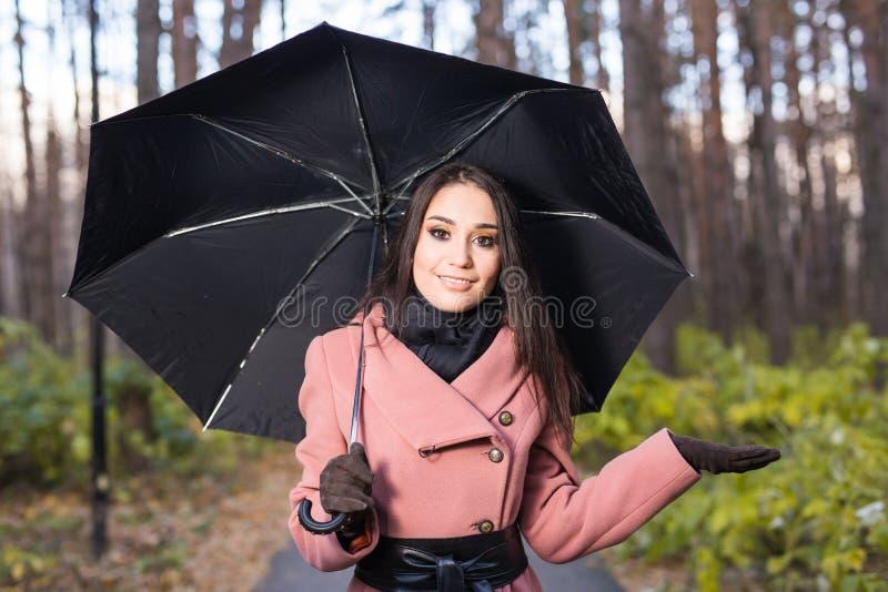 Femme heureuse avec le parapluie sous la pluie pendant la promenade en nature d'automne photos stock
