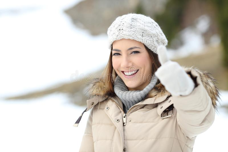 Femme heureuse avec le pouce maintenant chaud dans l'hiver photographie stock libre de droits