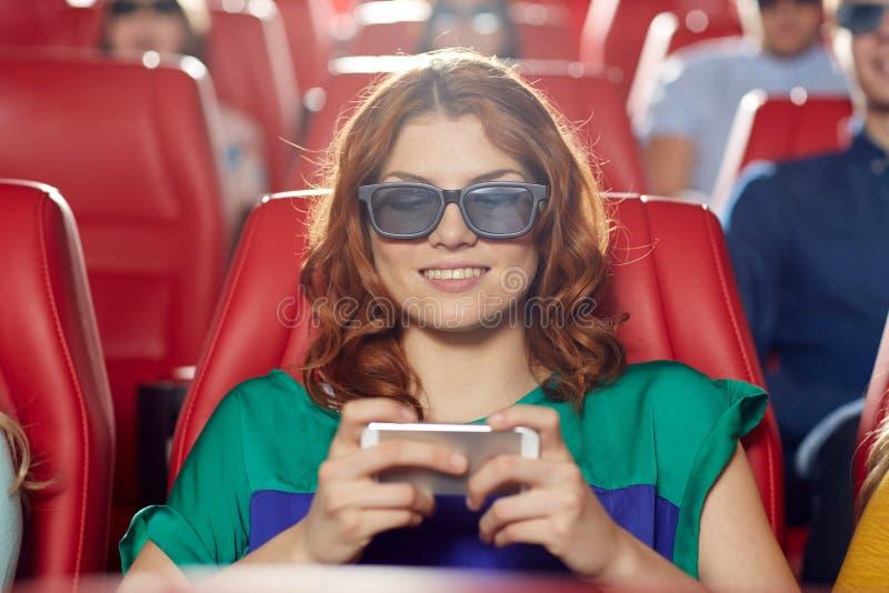 Femme heureuse avec le smartphone dans la salle de cinéma 3d photos stock