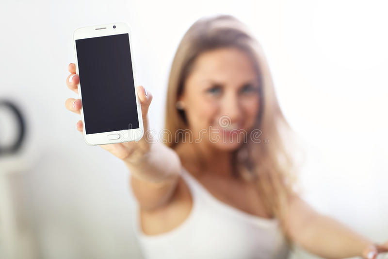 Femme heureuse avec le smartphone sur le sofa images stock