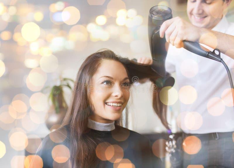 Femme heureuse avec le styliste faisant la coiffure au salon photo stock