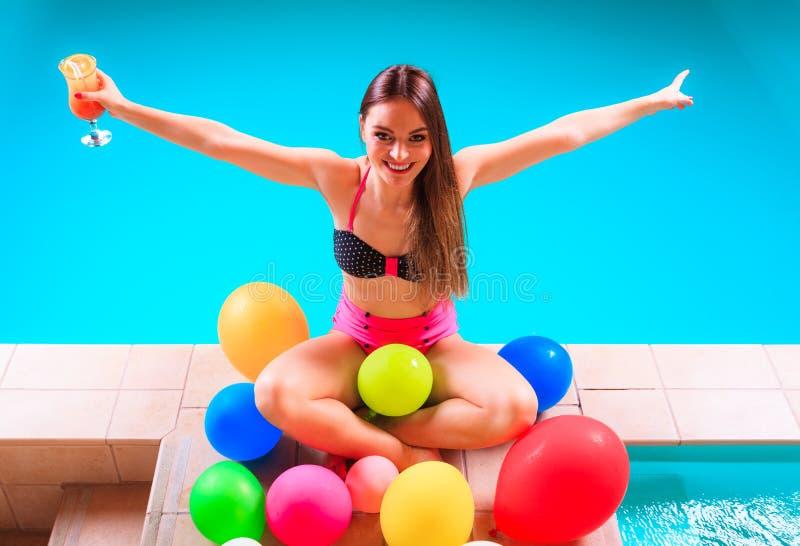 Femme heureuse avec les ballons et le cocktail au poolside image stock