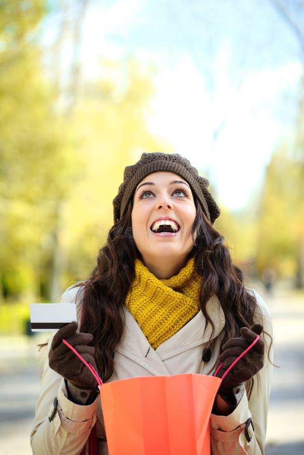 Femme heureuse avec les paniers et la carte de crédit image libre de droits