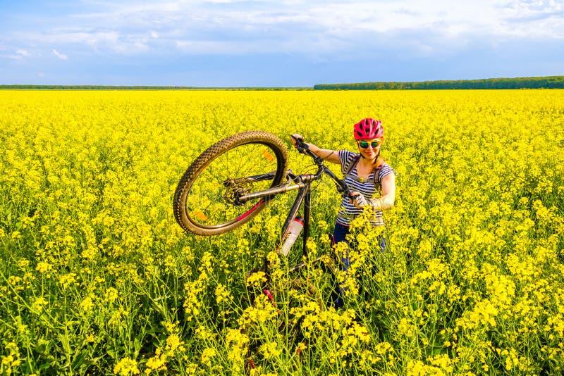 Femme heureuse avec une bicyclette dans un domaine de graine de colza, pendant une visite de vélo de campagne dans les régions ru photographie stock libre de droits