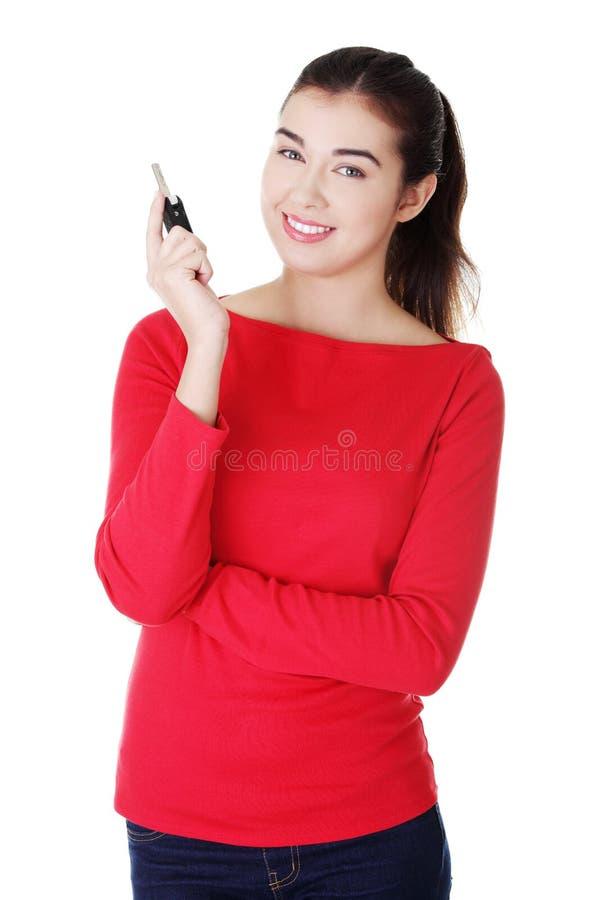 Femme heureuse avec une clé de véhicule. photographie stock libre de droits