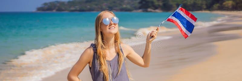 Femme heureuse ayant l'amusement ? la plage avec le drapeau de la Tha?lande Belle fille appréciant le voyage à la BANNIÈRE de l'A images stock