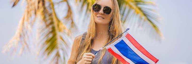 Femme heureuse ayant l'amusement ? la plage avec le drapeau de la Tha?lande Belle fille appréciant le voyage à la BANNIÈRE de l'A photo stock