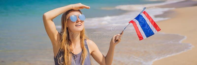 Femme heureuse ayant l'amusement ? la plage avec le drapeau de la Tha?lande Belle fille appréciant le voyage à la BANNIÈRE de l'A image libre de droits