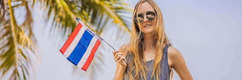 Femme heureuse ayant l'amusement ? la plage avec le drapeau de la Tha?lande Belle fille appréciant le voyage à la BANNIÈRE de l'A photos stock