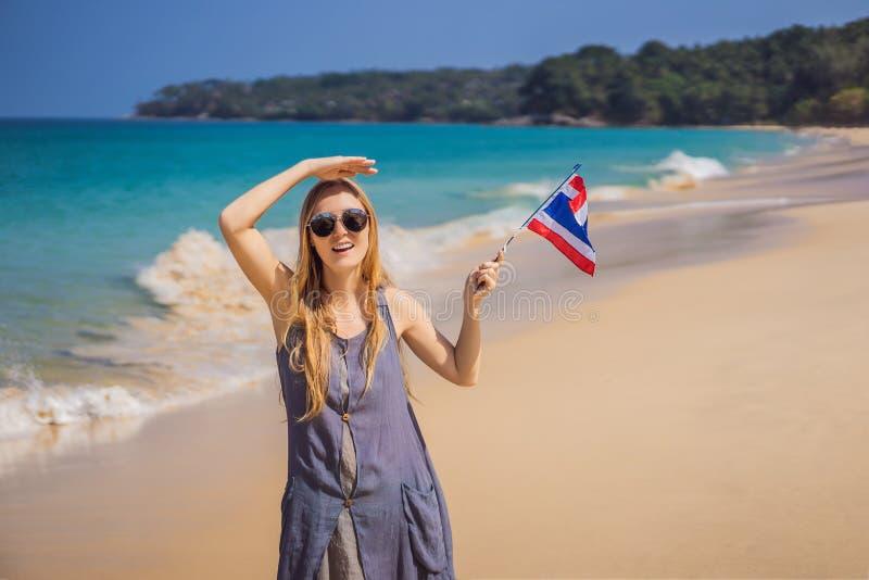 Femme heureuse ayant l'amusement ? la plage avec le drapeau de la Tha?lande Belle fille appr?ciant le voyage en Asie photographie stock