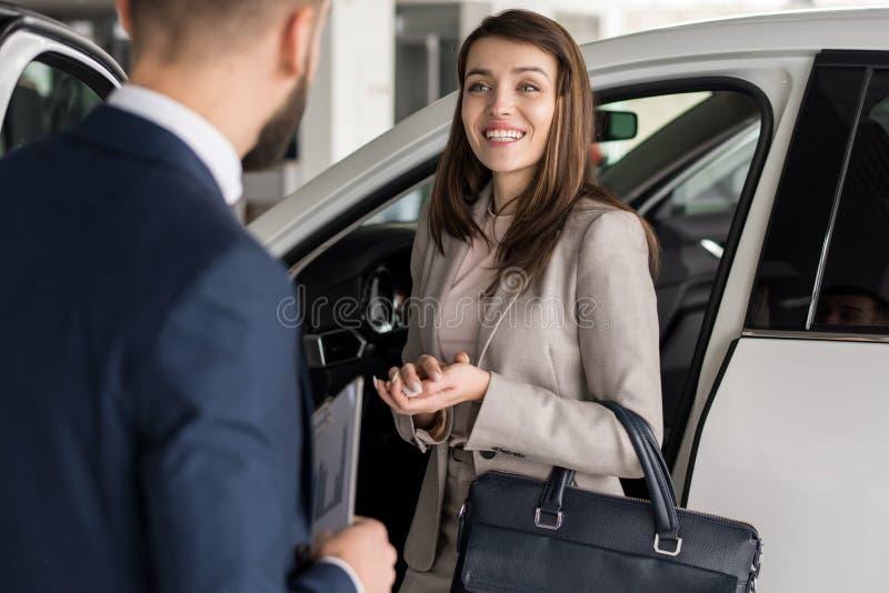 Femme heureuse choisissant la voiture dans la salle d'exposition photo stock