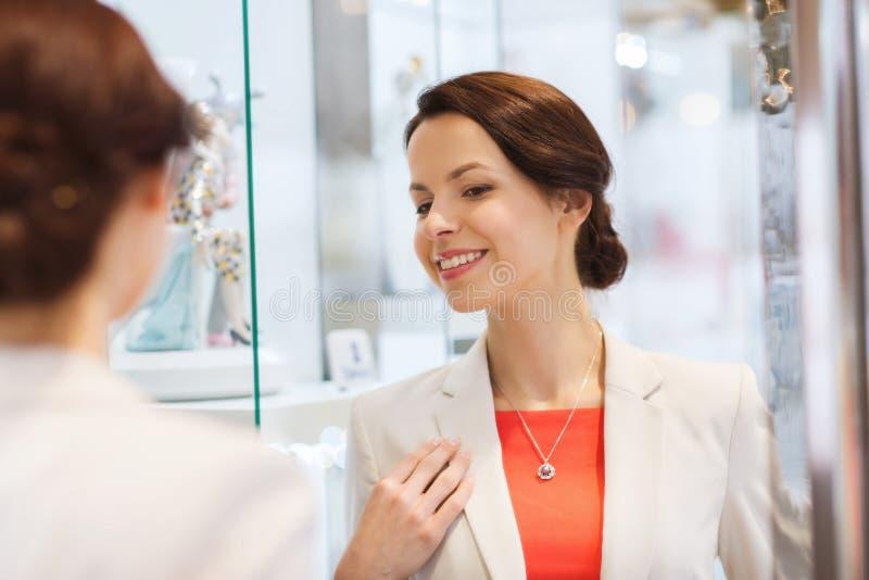 Femme heureuse choisissant le pendant au magasin de bijoux image libre de droits