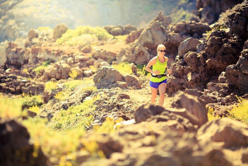 Femme heureuse courant dans le coucher du soleil d'été de montagnes photographie stock