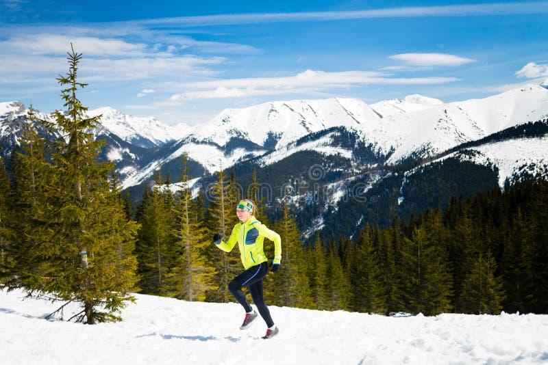 Femme heureuse courant en montagnes sur la neige d'hiver photographie stock