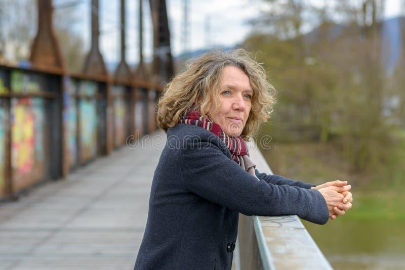 Femme heureuse décontractée se penchant sur un parapet de pont image libre de droits