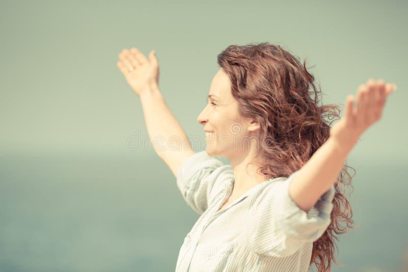Femme heureuse détendant à la plage images libres de droits