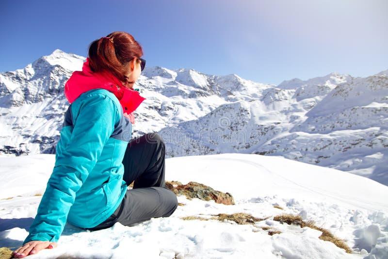 Femme heureuse détendant sur le dessus de la montagne sous le ciel bleu avec la lumière du soleil au jour d'hiver ensoleillé, vac images stock