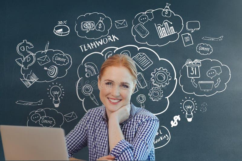 Femme heureuse d'affaires à un bureau utilisant un ordinateur sur le fond bleu avec des graphiques image libre de droits