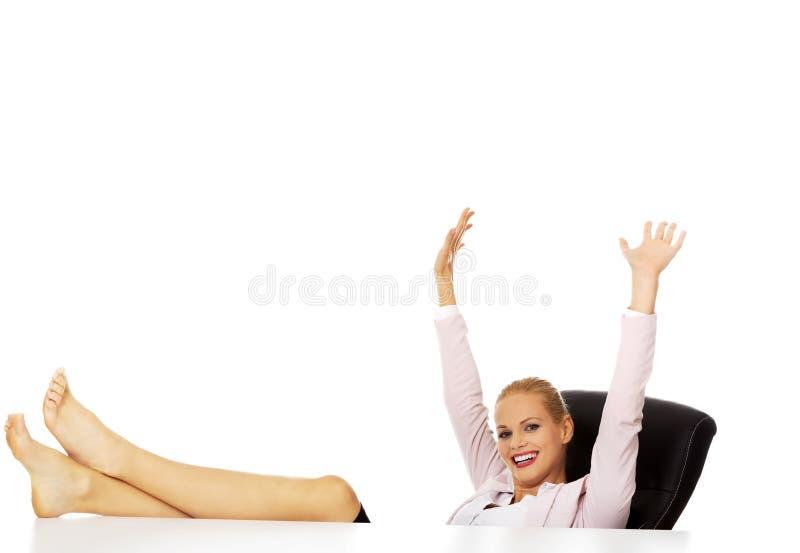 Femme heureuse d'affaires avec des mains tenant des jambes sur le bureau image stock