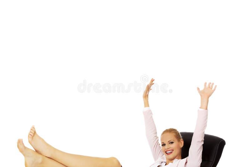 Femme heureuse d'affaires avec des mains tenant des jambes sur le bureau image libre de droits