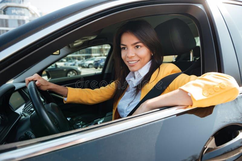 Femme heureuse d'affaires conduisant sa nouvelle voiture photos libres de droits