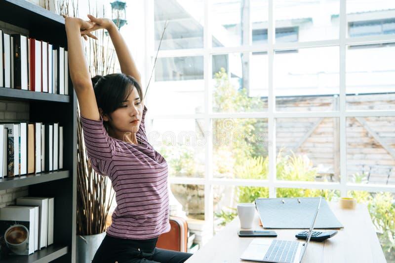 Femme heureuse d'affaires détendant et s'étirant dans le bureau photographie stock
