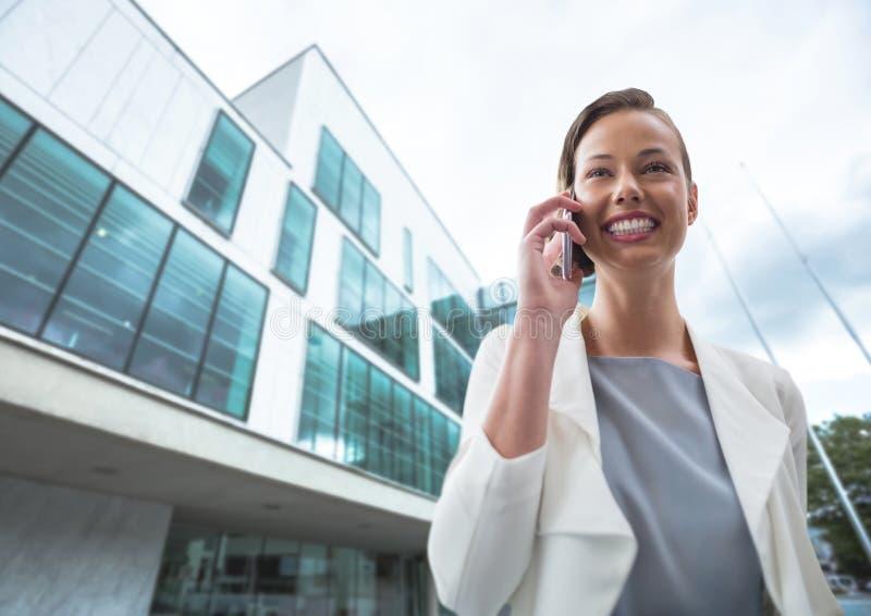 Femme heureuse d'affaires parlant au téléphone sur le fond de bâtiment photographie stock libre de droits
