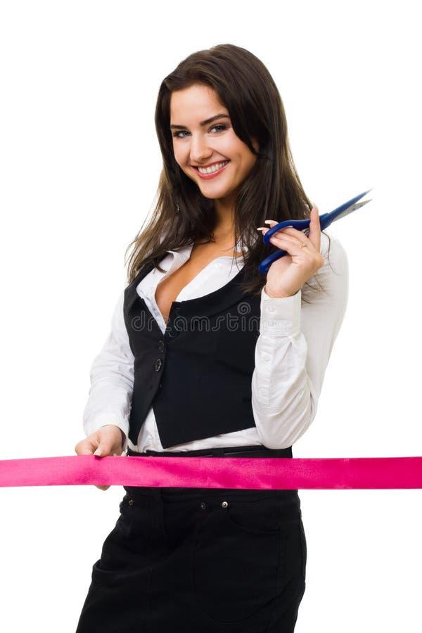 Femme heureuse d'affaires prête à couper la bande rouge image libre de droits
