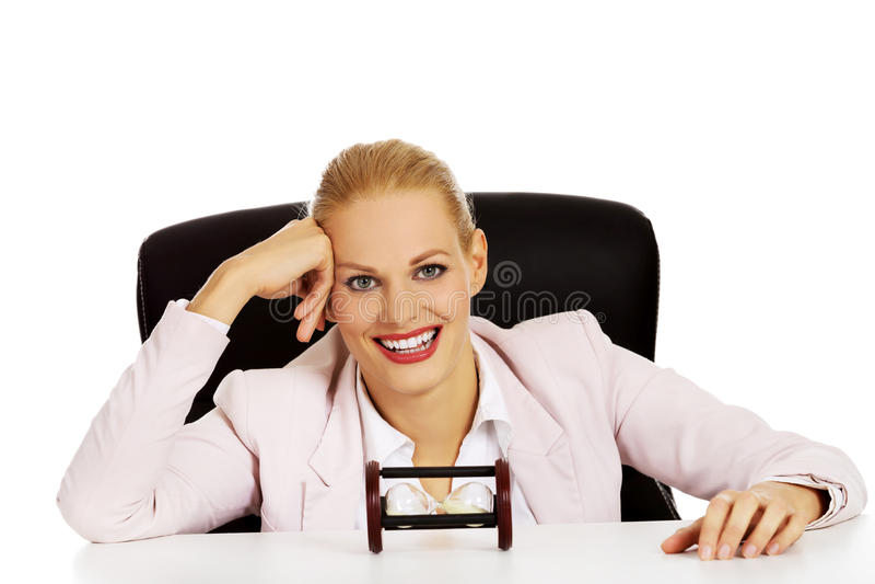 Femme heureuse d'affaires s'asseyant derrière le bureau avec des sandglass images stock