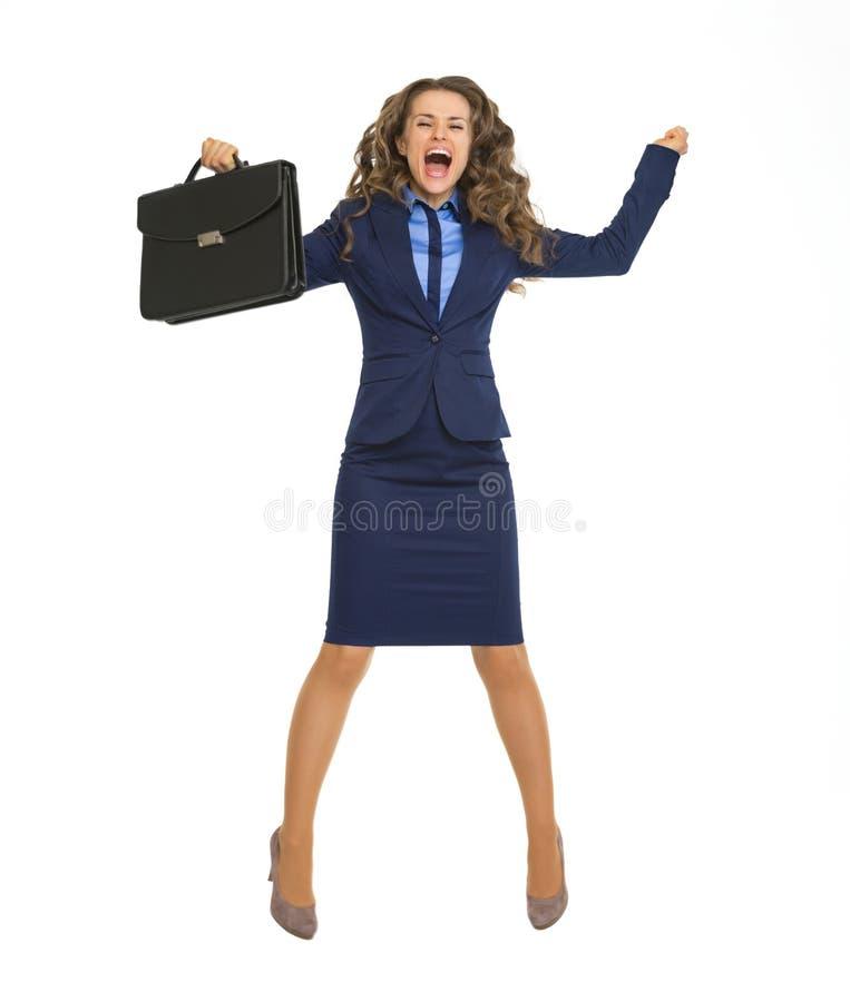 Femme heureuse d'affaires sautant avec la serviette photo stock