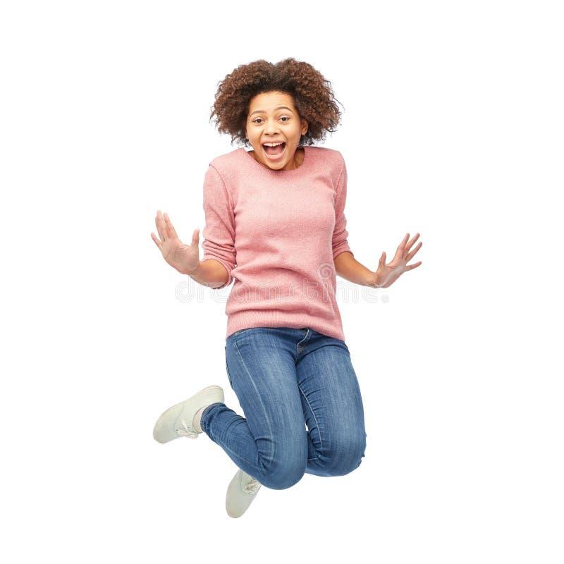 Femme heureuse d'afro-américain sautant par-dessus le blanc photo libre de droits