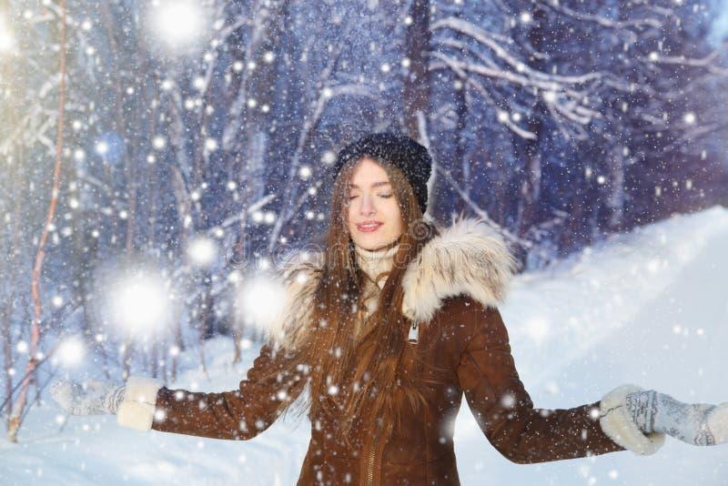 Femme heureuse d'amusement d'hiver jouant la neige de lancement avec des bras vers le haut d'ouvert dans la liberté appréciant la photographie stock
