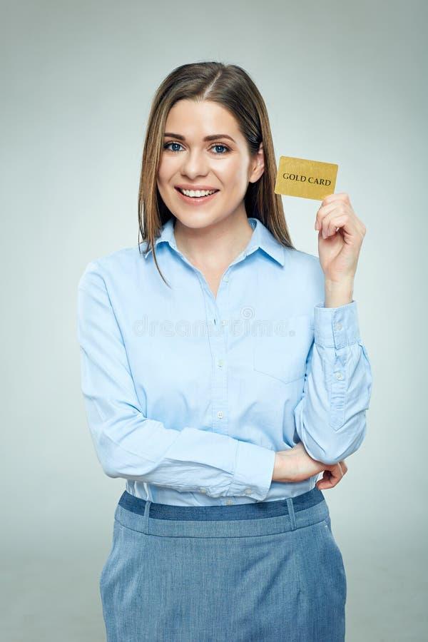 Femme heureuse d'emloyee de banque tenant la carte de crédit d'or photographie stock libre de droits