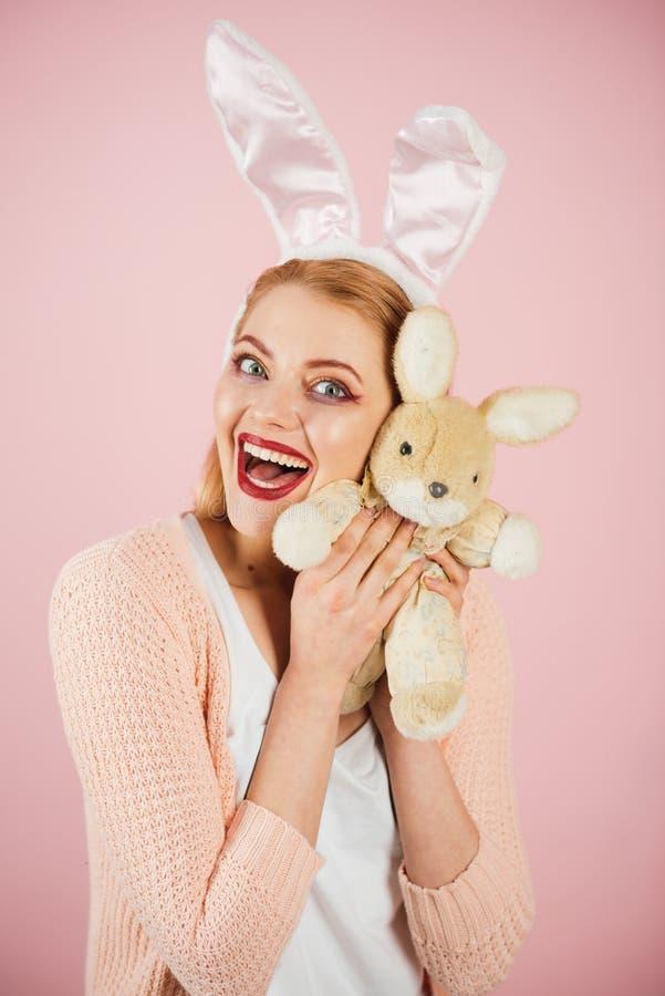 femme heureuse dans des oreilles de lapin avec le jouet Vacances de ressort Fille avec le jouet de lièvres Femme dans des oreille photo libre de droits