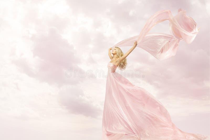 Femme heureuse dans la longue robe rose, tissu en soie d'écharpe de vol de fille photographie stock libre de droits