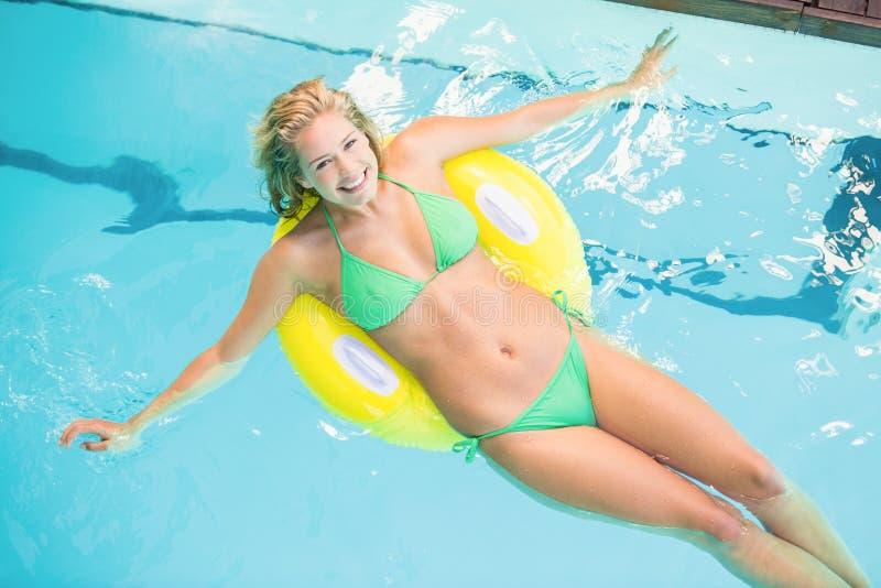 Femme heureuse dans le bikini vert détendant sur le tube gonflable dans la piscine photo libre de droits