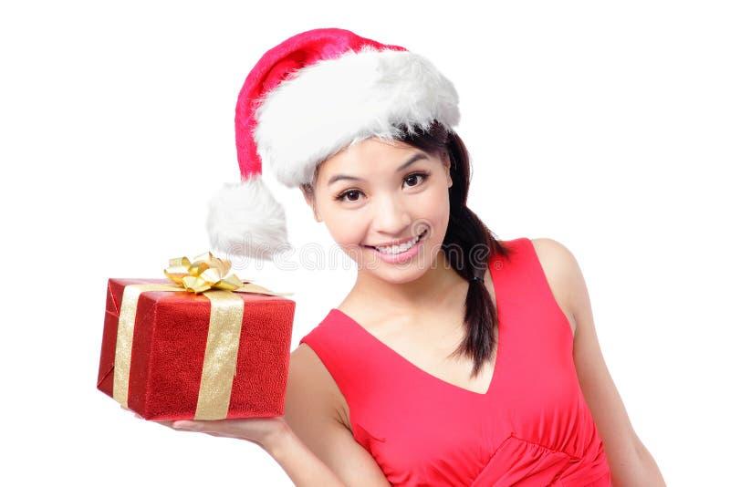 Femme heureuse dans le chapeau de Santa affichant le cadeau de Noël photos stock