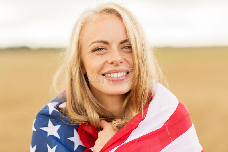 Femme heureuse dans le drapeau américain sur le gisement de céréale image libre de droits
