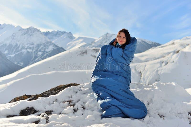 Femme heureuse dans le sac de couchage en montagnes neigeuses photographie stock libre de droits