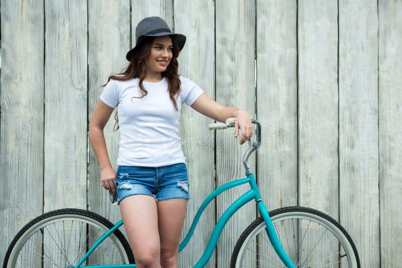 Femme heureuse dans le T-shirt blanc et le pantalon chaud avec la bicyclette image libre de droits