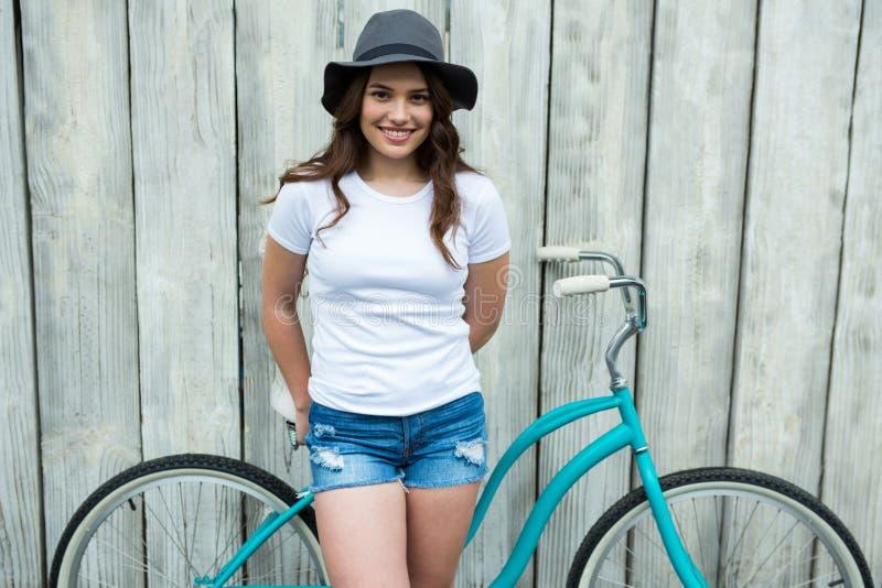 Femme heureuse dans le T-shirt blanc et le pantalon chaud avec la bicyclette photographie stock